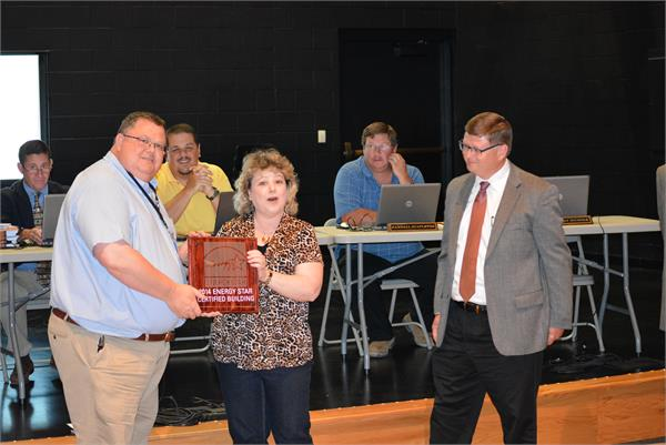 BCHS receives Energy Star Award. Karen Curnutte, center, presents the plaque to Principal, Dan Imes as Managing Architect Kevin Cheek looks on.