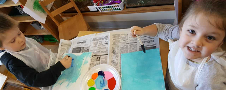 Preschool boy, at left, and a preschool girl, at right, enjoy painting.