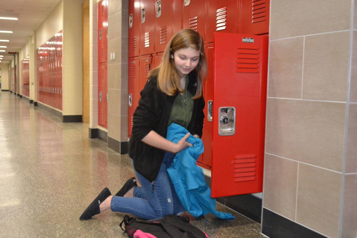 Eighth grader Ashley Stewart stows her books in her new locker.