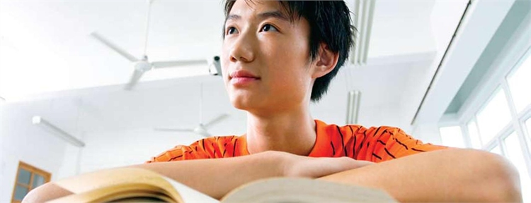 high school student close up looking over his textbook. (Stock photo)