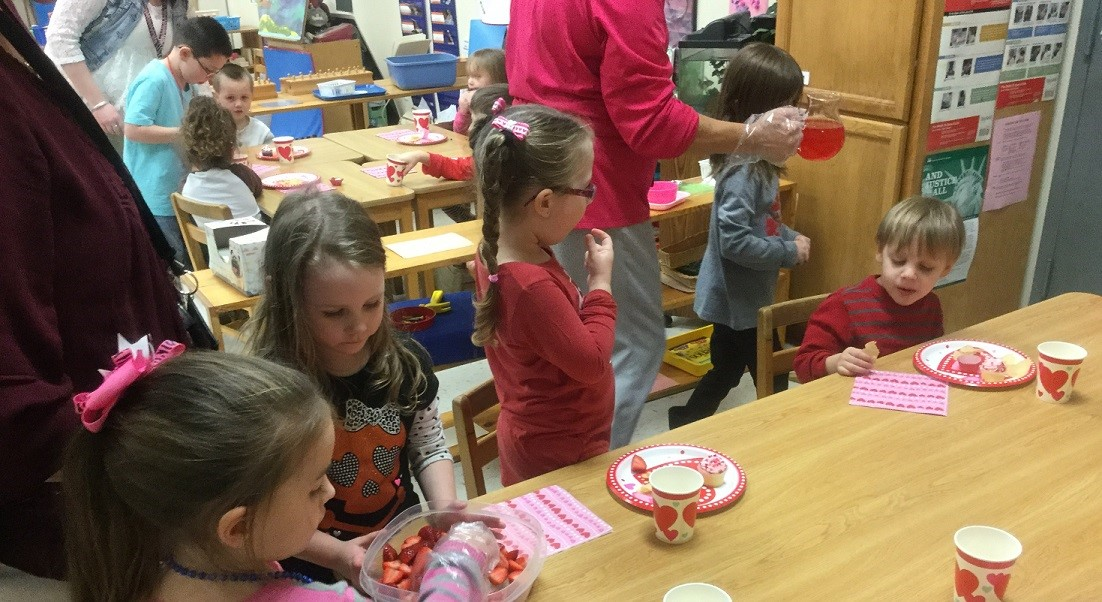 Preschool students practice serving others during Valentines exchange.