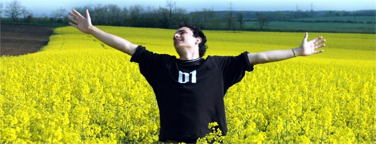 High school boy standing in a field of yellow flowers with his hand outstretched. (Stock photo)