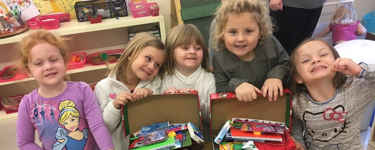 Preschool students are all smiles while they are preparing shoe boxes for Operation Christmas Child.