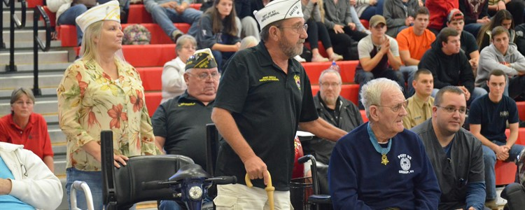 Veteran's stand and are recognized during the playing of their military branch service song.
