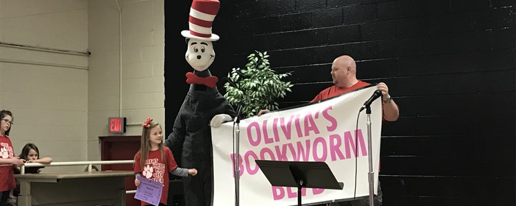 Mr. Salyers gets some help holding a banner from the Cat in the Hat and a student.