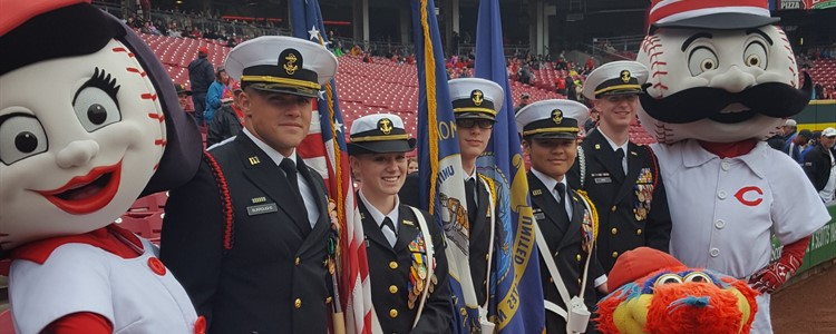The NJROTC Color Guard presented at the Cincinnati Reds game. Left to right: Brandon Burroughs, Angela Chandler, Jacob Smith, Spencer Cash and Chris Rice. Reds mascots Rosy-the-Red; Gapped (kneeling) and right is Mr. Red Legs.