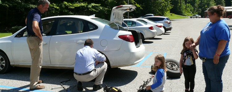 Super Tire Change! Our Superintendent (kneeling) lends a hand to a passerby by changing her tire for her.