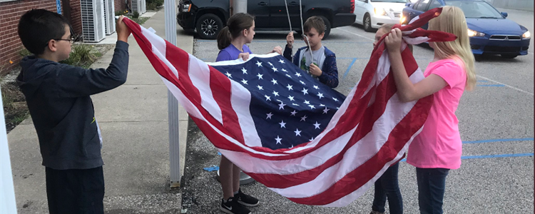 Students carefully and respectfully fold the flag. Flags were donated by Kathy Kazee (retired Secretary to the Superintendent) for all our schools and the district office.
