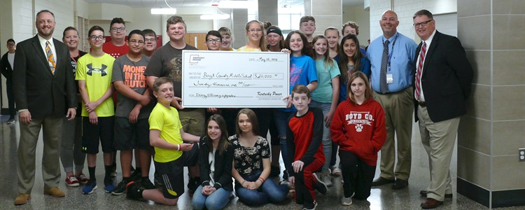 Middle School students pose with a check for $20,000 from KY Power. It was earned by installing upgrades to lighting and HVAC. Far left, Aaron Shultz. Far right is Kevin Cheek. Next to Kevin is Interim Superintendent Bill Boblett.