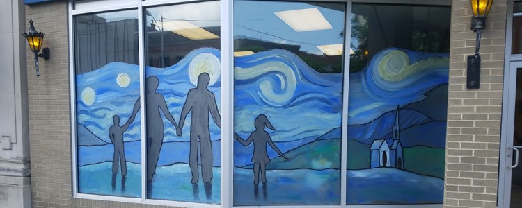 "Students of Arts and Humanities Department Head Mike Spears painted windows downtown for Braidy's theme ""family"" for first Friday next week."