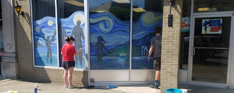 "Students of Arts and Humanities Department Head Mike Spears painted windows downtown for Braidy's theme ""family"" for First Friday."