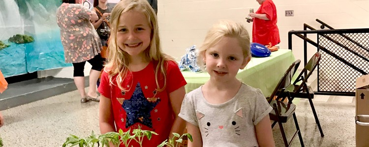 Two students pause for a picture during Catlettsburg Elementary's Summer Food Fun event. In the foreground are tomatoes from a local grower.
