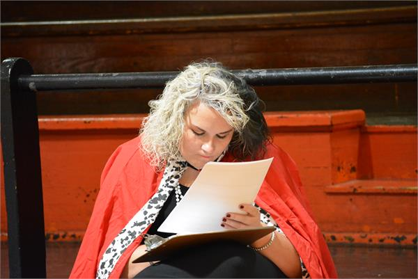 A teacher dressed as Cruella Deville takes a moment to read through some papers.