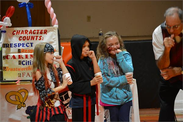 Three Catlettsburg students following the magician's directions and 'blowing up' their thumbs like a balloon.