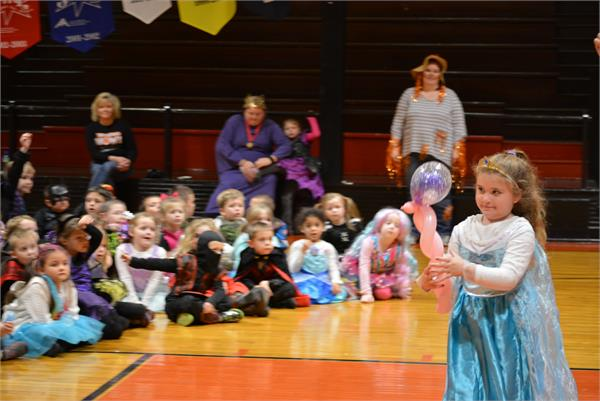 A student dressed as a princess chooses a balloon sculpture that looks like a scepter.