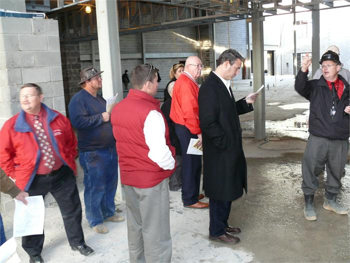 Kevin Cheek, far right, leads the tour of the construction site.